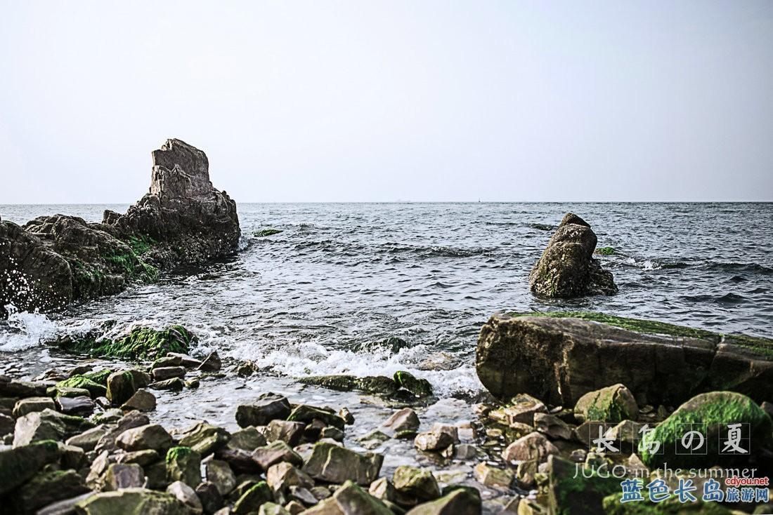 稍作休息后我们首先来到第一站月牙湾。此为月牙湾标志性建筑物后羿射日。如果不是穿着裙子我觉得我应该会摆一个和他一样的姿势拍照吧。我们住的渔家乐是在嵩前村,也是离月牙湾最近的一个村,走过来步行只需要十多分钟。  月牙湾进口附近就是海豹苑,里面有很多野生斑海豹,可以买点食物喂它们。你看它们这样子,是不是萌萌哒。  步入月牙湾公园,你就踏上了一条长长的用滩上鹅卵石铺就的石毯。石毯选料圆润,晶莹如珠,造型色彩相间,凹凸不平,赤足走上去,就感觉着有一种不可名状的惬意。我想月牙湾得名,应该就是像月牙形状的海岸线吧。